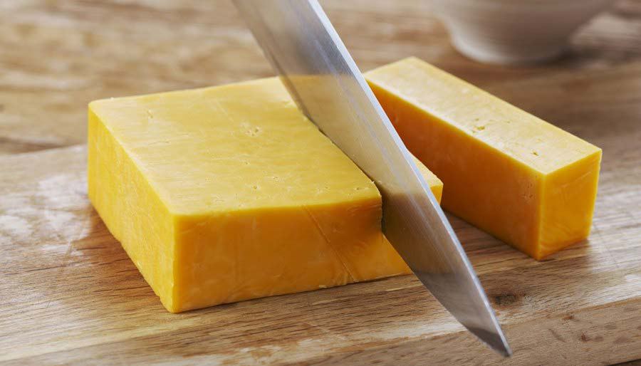 Cheddar being sliced