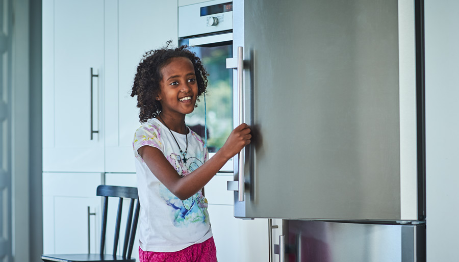happy girl opening fridge