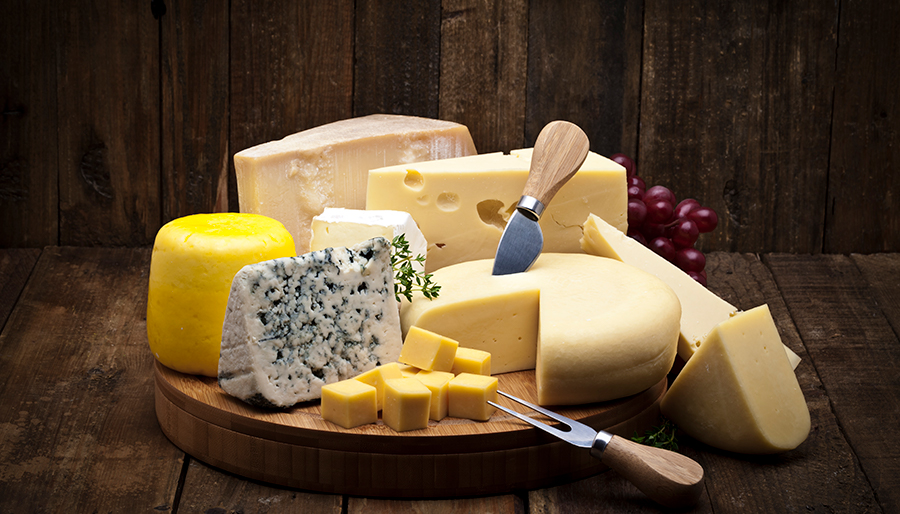 Various cheeses on round wooden board