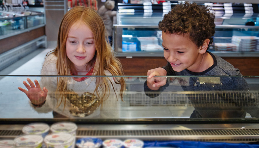 a boy and girl browse supermarket wares